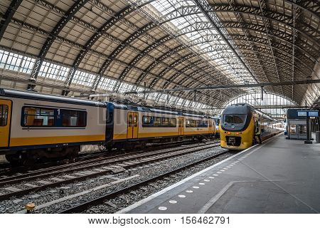 Amsterdam Netherlands - August 1 2016: Interior view of Central Station in Amsterdam with yellow trains on platforms.