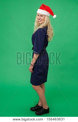Young blonde woman in a christmas cap looking coquettishly and smiling chroma key green screen