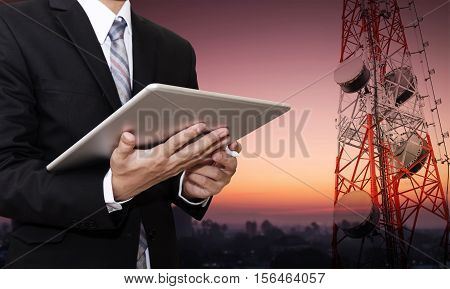 Businessman working on digital tablet, with satellite dish telecom network on telecommunication tower at countryside city in sunrise morning, telecommunication in business and development