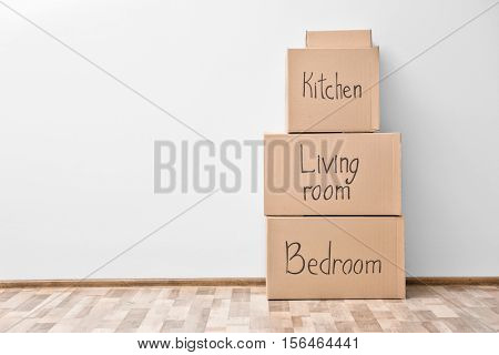 Empty room with moving boxes on wall background
