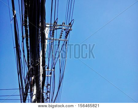 High voltage power pole with wires tangled and communication pole from bottom side on blue sky background