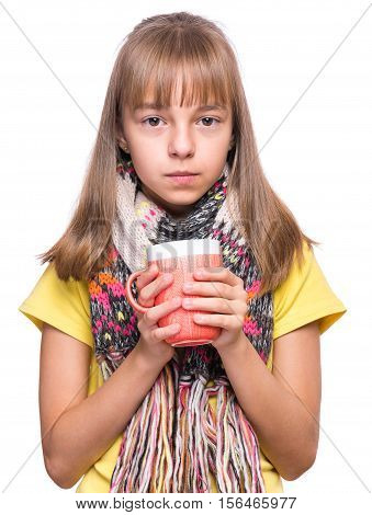 Healthcare and medicine concept - ill little girl with flu holding cup of hot tea or milk. Unhappy kid with mug, isolated on white background. Sad child wearing yellow t-shirt and scarf drinks water.