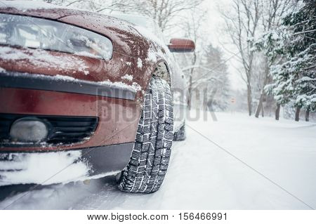 Car on forest road covered with snow. From ground view selective focus on winter tires