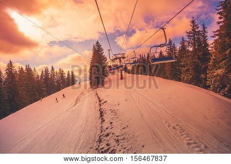 Winter mountains panorama with ski slopes and ski lifts in a cloudy day. Sunset soft light with dramatic orange sky. Vintage toning effect. Bukovel, Carpathians, Ukraine, Europe