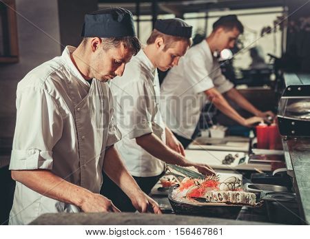 Three male cooks dressed in black aprons and hats preparing sushi set in the interior of modern professional kitchen
