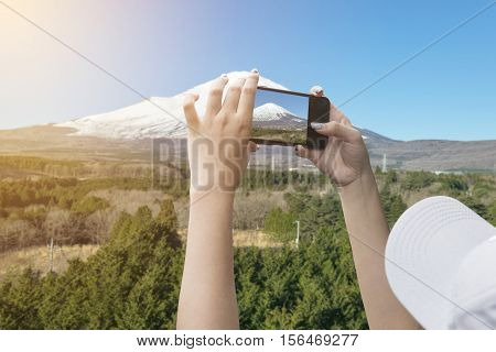 Hand of a woman taking a picture of Mount Fuji with a smart phone.