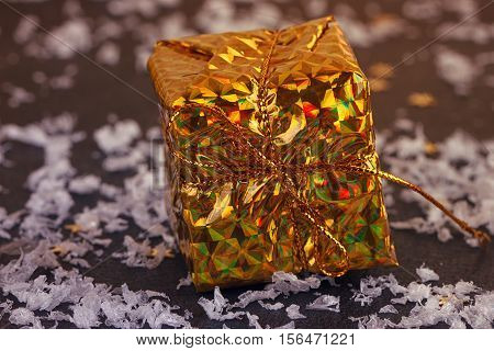 Gold box with gifts. On black background