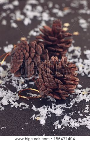 Three Pine cones on the black slate background
