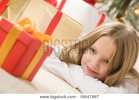 Pretty blonde hair girl looking at small red gift with gold ribbon. Christmas tree and bunch of presents in background