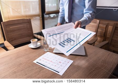 Working plan. Close up of printed documents with statistics and graphics being in hands of responsible hard working male office worker