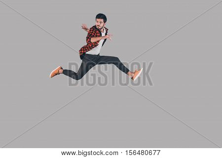 Man in mid-air. Mid-air shot of handsome young man jumping and gesturing against background