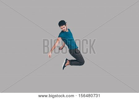 Carefree jumping. Mid-air shot of handsome young man in cap jumping and gesturing against background