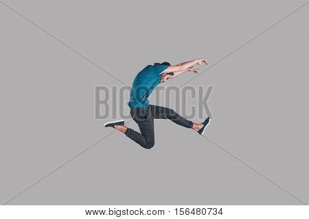 Freedom in moving. Mid-air shot of handsome young man in cap jumping and gesturing against background
