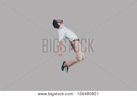 Hovering in air. Mid-air shot of handsome young man jumping and gesturing against background