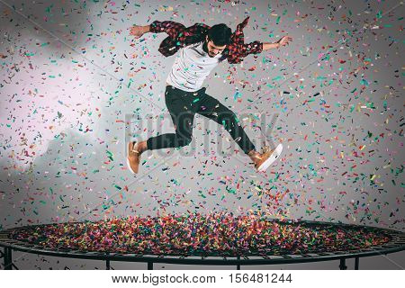 Colorful fun. Mid-air shot of handsome young man jumping on trampoline with confetti all around him