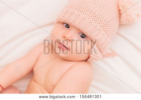 adorable 5 months old baby girl wearing knitted hat and looks at the camera