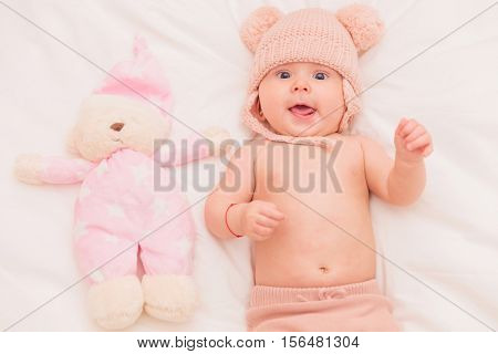 super excited five months old baby girl wearing knitted hat near toy teddy bear