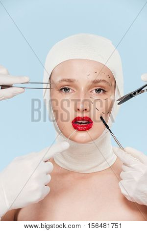 Model with surgical instruments. looking at camera. isolated biege background