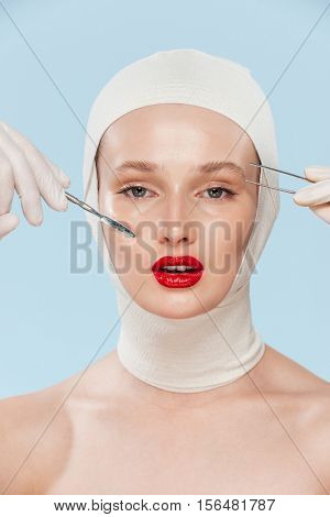 Beautiful model with unusual image. with medical instruments. isolated biege background