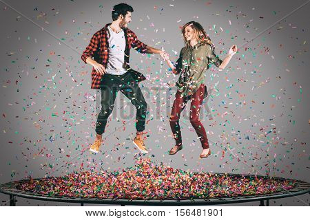 Colorful fun. Mid-air shot of beautiful young cheerful couple holding hands while jumping on trampoline together with confetti all around them