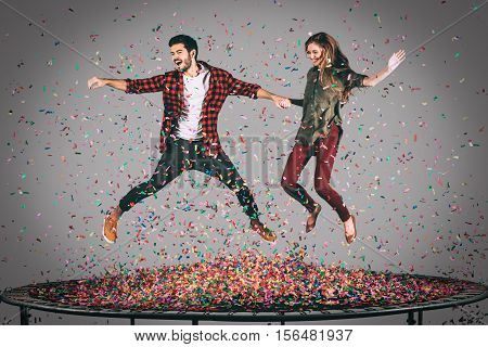 Enjoying fun time together. Mid-air shot of beautiful young cheerful couple holding hands while jumping on trampoline together with confetti all around them