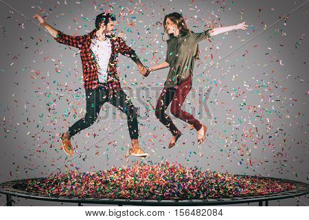 They love having fun. Mid-air shot of beautiful young cheerful couple holding hands while jumping on trampoline together with confetti all around them
