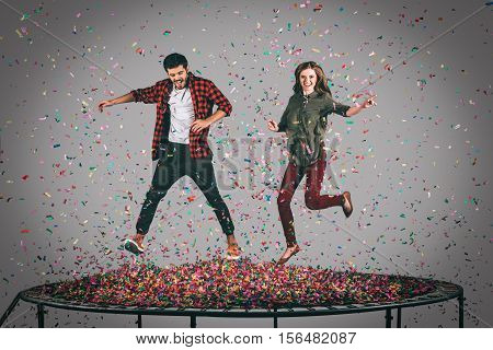 Fun time. Mid-air shot of beautiful young cheerful couple jumping on trampoline together with confetti all around them