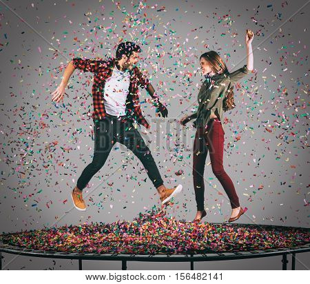 Fun time together. Mid-air shot of beautiful young cheerful couple jumping on trampoline together with confetti all around them
