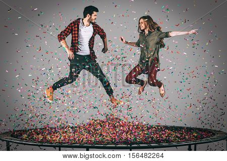 Enjoying confetti fun. Mid-air shot of beautiful young cheerful couple jumping on trampoline together with confetti all around them