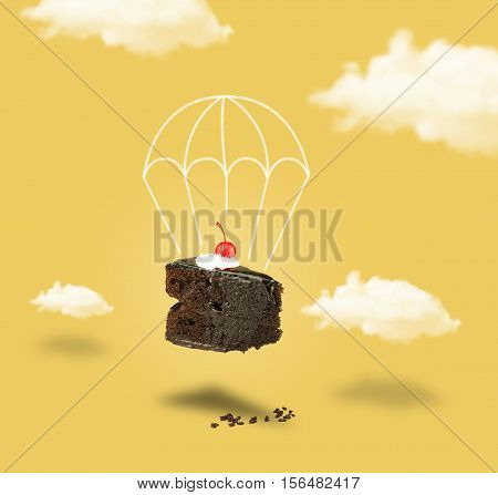 Isolated Chocolate cherry cake with parachute on yellow sky background. Chocolate pie. Flying brownie with cream. Chocolate cherry cake with parachute without text.