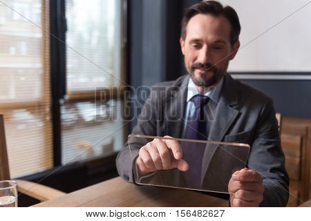 Involved in the activity. Serious nice diligent man holding a tablet and working on it while being at the office
