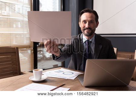 Look at it. Happy handsome good looking man sitting in front of the laptop and smiling while showing you a sheet of paper