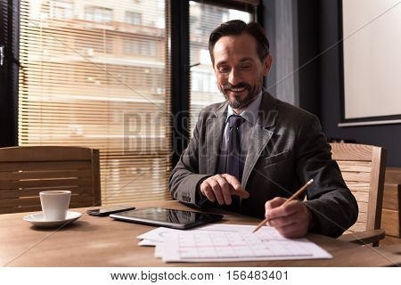 Plan your timetable. Pleasant nice responsible man holding a pencil and looking at the calendar while planning his timetable