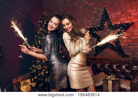 Two girls in a beautiful dress dancing and smiling with a sparkle. Happy Hew 2017 year! Warmest Wishes For Christmas!