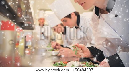 Snow falling against chef finishing her salad in culinary class