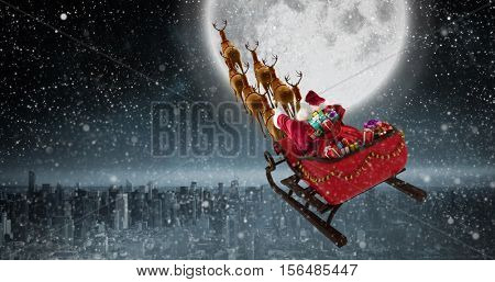 High angle view of Santa Claus riding on sled with gift box against balcony overlooking city