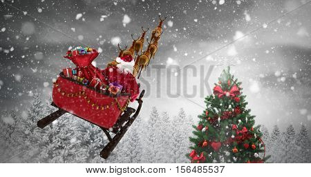 High angle view of Santa Claus riding on sled during Christmas against christmas tree in snowy forest