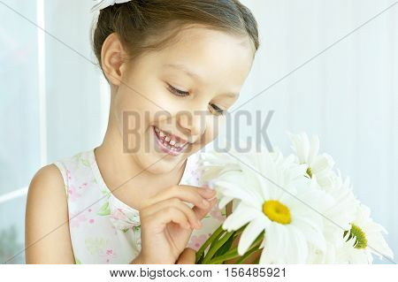 Portrait of a Beautiful little girl with dasies flowers