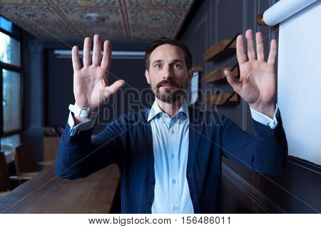 Invisible screen. Delighted nice positive man standing in the room and pressing hands to the virtual sensory panel while looking in front of him