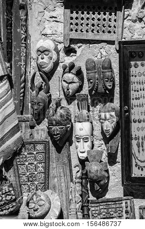 Touristic souvenir shop in the middle of Medina quarter in Essaouira Morocco. Stylish wooden masks on the wall other craft. Black and white