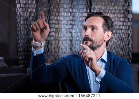 Futuristic device. Handsome nice brunette man sitting and holding his hands up while touching the virtual sensory screen