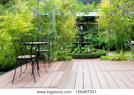 Black chair in wood patio at green garden with fountain in house. Outdoor garden.