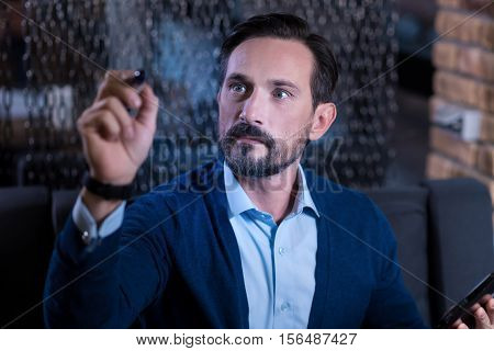 New technological advances. Serious handsome adult man looking at his hand and writing something on the virtual screen panel while working with modern technology