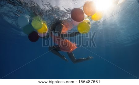 Underwater shoot of flying  woman with multicolored balloons