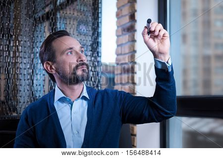 Interesting object. Serious handsome confident man holding a highlighter and looking at it while sitting near the window