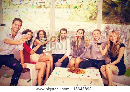 Portrait of friends having cocktail drinks against flying colours