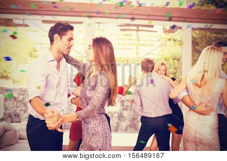 Couple embracing each other while dancing against flying colours