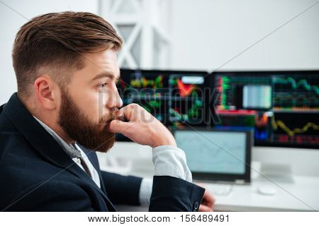Thoughtful bearded young businessman working and thinking ay workplace in office