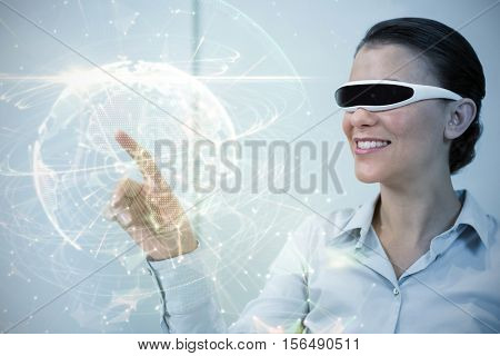 Global technology background in green against cheerful businesswoman with virtual reality simulator