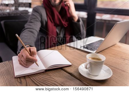 Making notes. Selective focus of a notebook being designed for making notes with a man in the background holding a pencil while intending to write something
